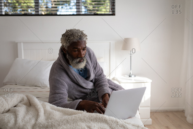 African American senior man lying on a bed in a bedroom, using a laptop, social distancing and self isolation in quarantine lockdown