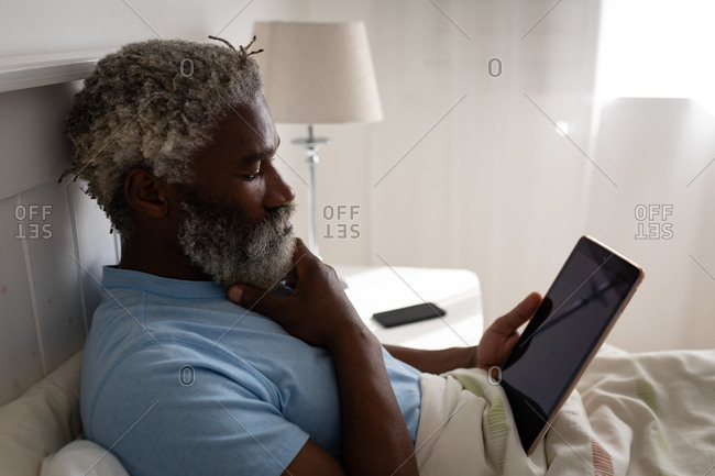 African American senior man lying on a bed in a bedroom, using a digital tablet, rubbing his chin, social distancing and self isolation in quarantine lockdown
