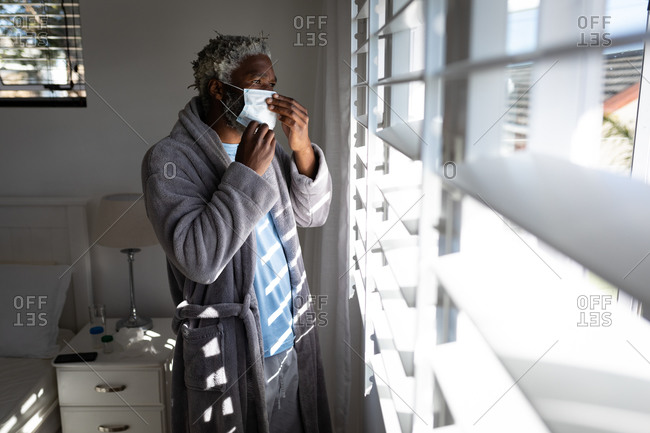African American senior man standing in a bedroom, putting a face mask on, looking through a window, social distancing and self isolation in quarantine lockdown