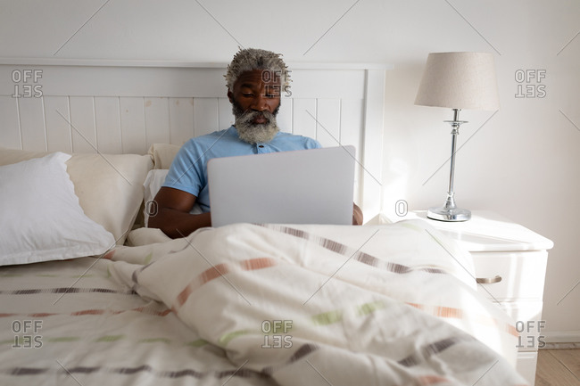 African American senior man lying on a bed in a bedroom, using a laptop and smiling, social distancing and self isolation in quarantine lockdown