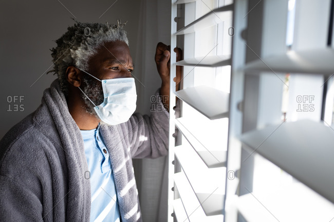 African American senior man standing in a bedroom, wearing a face mask, looking through a window, social distancing and self isolation in quarantine lockdown
