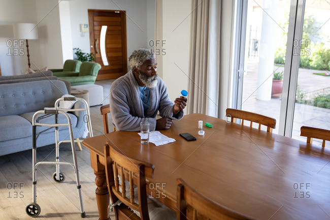 African American senior man sitting by a table in a living room, holding two medical pills and a glass of water in his hands, social distancing and self isolation in quarantine lockdown