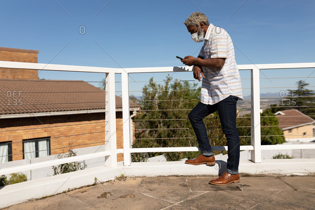 African American senior man standing on a balcony, using a smartphone, social distancing and self isolation in quarantine lockdown