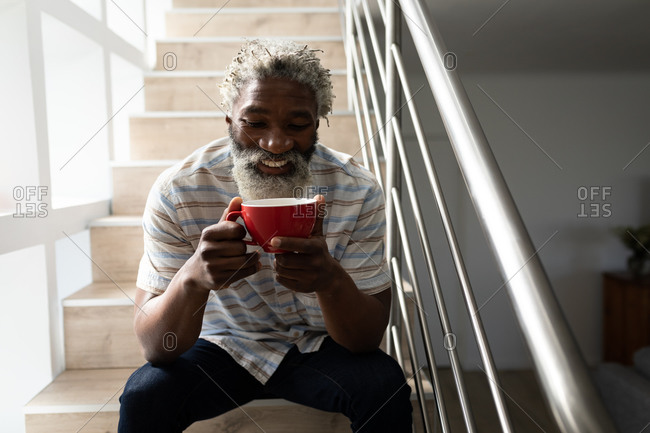 African American senior man sitting on stairs, holding a cup of coffee and smiling, social distancing and self isolation in quarantine lockdown