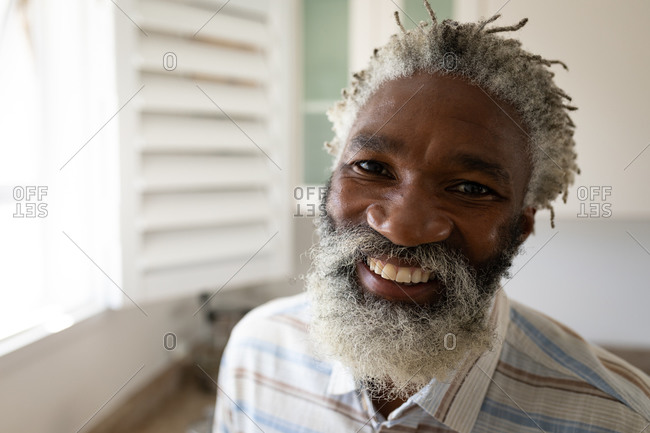Portrait of an African American senior man standing in a bedroom, looking at the camera and smiling, social distancing and self isolation in quarantine lockdown