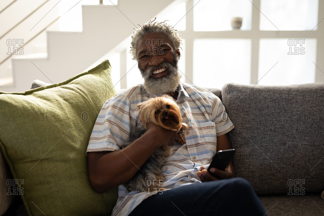 African American senior man sitting on a couch, using a smartphone, taking a selfie, social distancing and self isolation in quarantine lockdown