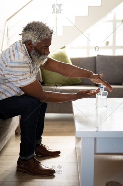 African American senior man sitting on a couch, pouring soap on his hands, social distancing and self isolation in quarantine lockdown
