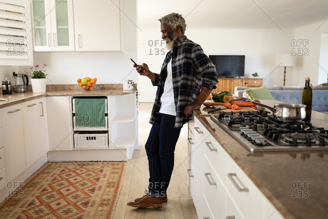 African American senior man standing in a kitchen, using a smartphone, social distancing and self isolation in quarantine lockdown