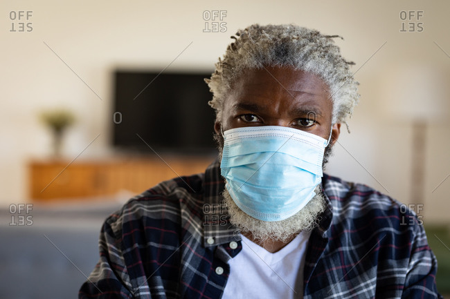 Portrait of an African American senior man sitting, wearing a face mask, social distancing and self isolation in quarantine lockdown