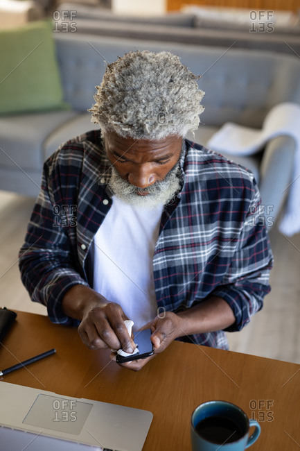 African American senior man sitting by a table, cleaning a smartphone with a tissue, social distancing and self isolation in quarantine lockdown