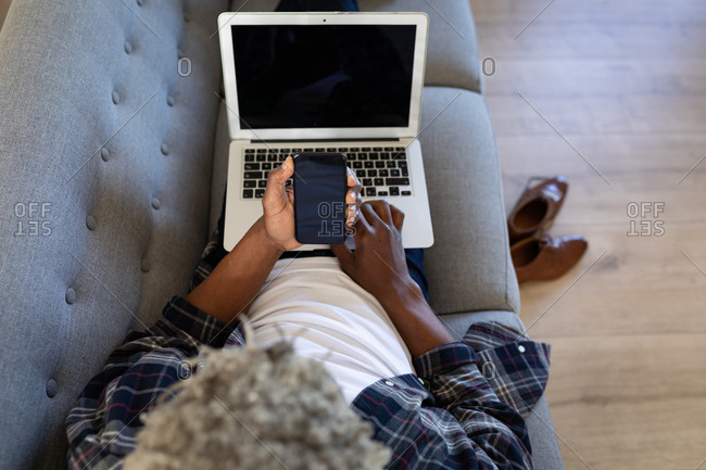 African American senior man lying on a couch, using a laptop, talking on a phone, social distancing and self isolation in quarantine lockdown