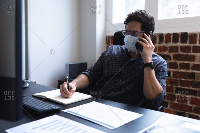 Caucasian man working in a casual office, talking on smartphone, taking notes and wearing face mask. Social distancing in the workplace during Coronavirus Covid 19 pandemic.