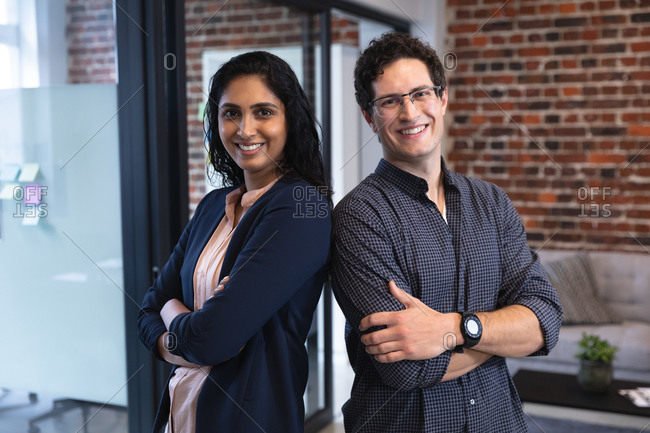 Portrait of mixed race woman and Caucasian man working in a casual office, smiling and looking at camera. Creative business professionals working in a busy modern office.