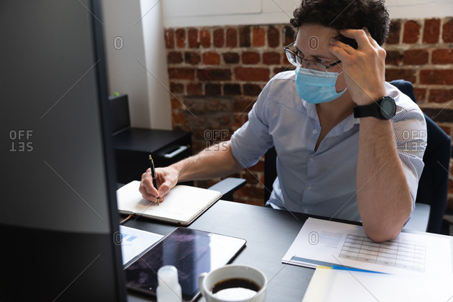 Caucasian man working in a casual office, taking notes and wearing face mask. Social distancing in the workplace during Coronavirus Covid 19 pandemic.