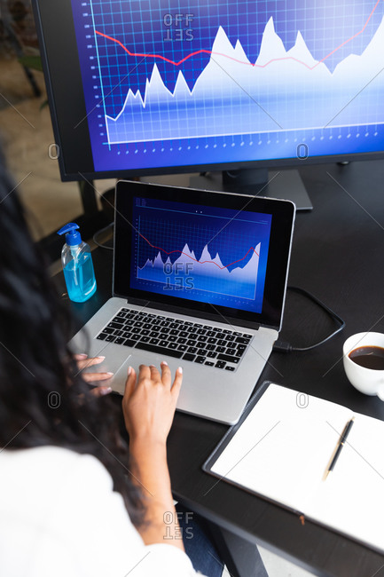 Mixed race woman working in a casual office, using her laptop and looking at graphs. Social distancing in the workplace during Coronavirus Covid 19 pandemic.