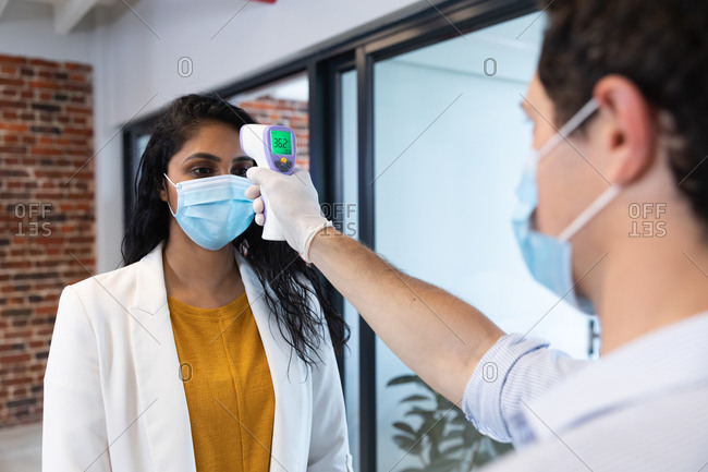 Mixed race woman and Caucasian man working in a casual office, wearing face masks, a man taking her temperature. Social distancing in the workplace during Coronavirus Covid 19 pandemic.