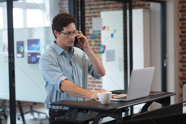 Caucasian man working in a casual office, talking on a smartphone and using a laptop computer. Social distancing in the workplace during Coronavirus Covid 19 pandemic.