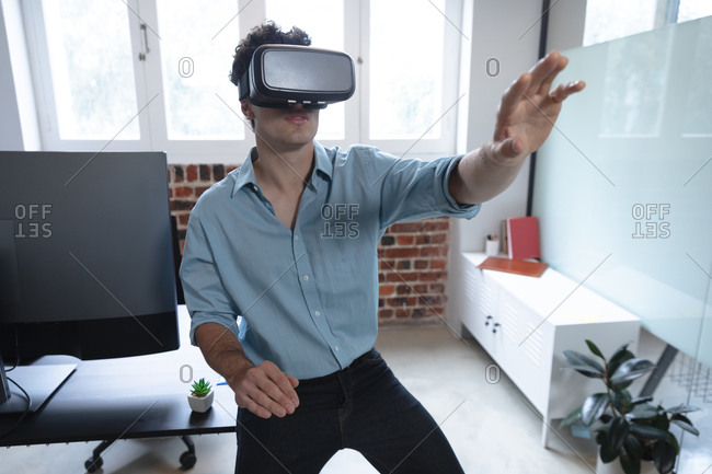 Caucasian man working in a casual office, wearing vr headset, touching virtual screen. Social distancing in the workplace during Coronavirus Covid 19 pandemic.