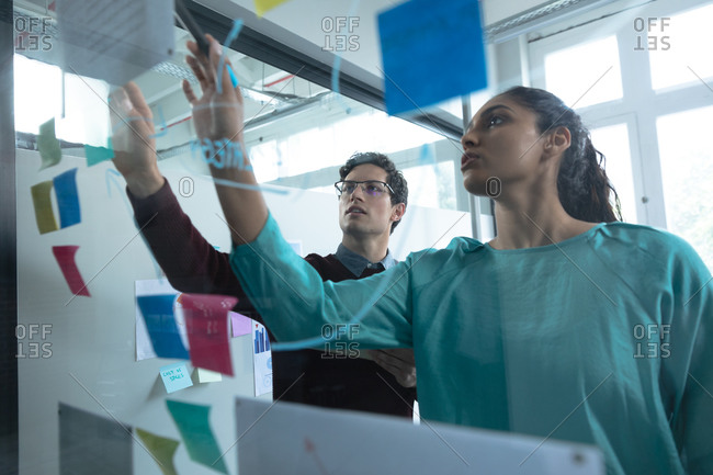 Mixed race woman and Caucasian man working in a casual office, writing on a glass board and talking. Creative business professionals working in a busy modern office.