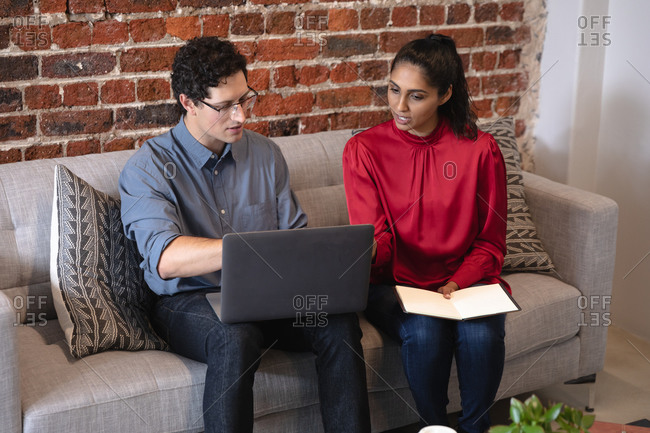 Mixed race woman and Caucasian man working in a casual office, sitting on a sofa, using a laptop computer and talking. Creative business professionals working in a busy modern office.