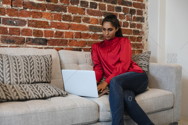Mixed race woman working in a casual office, sitting on a sofa, using a laptop computer. Social distancing in the workplace during Coronavirus Covid 19 pandemic.