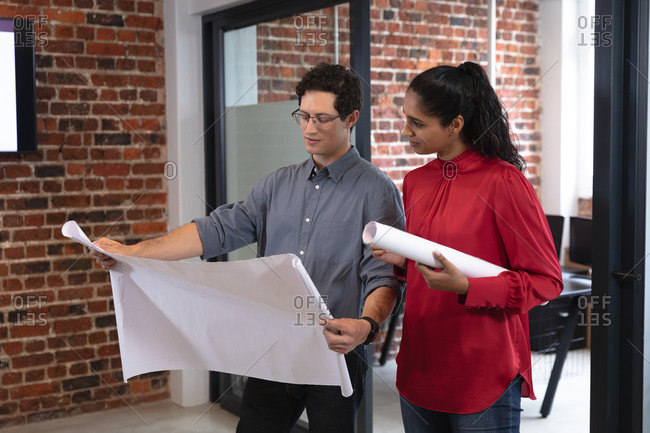 Mixed race woman and Caucasian man working in a casual office, holding plans and talking. Creative business professionals working in a busy modern office.