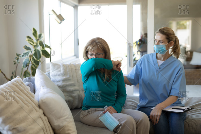 Caucasian woman being visited at home by a Caucasian female nurse, covering mouth while coughing, the nurse wearing face mask. Medical care at home during Covid 19 coronavirus quarantine.