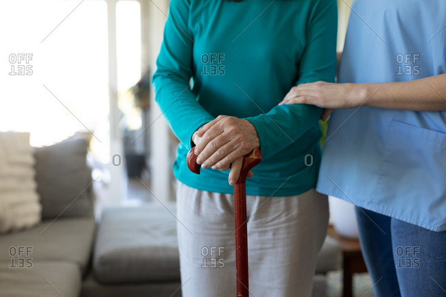 Senior Caucasian woman at home visited by Caucasian female nurse, standing with a cane. Medical care at home during Covid 19 Coronavirus quarantine.