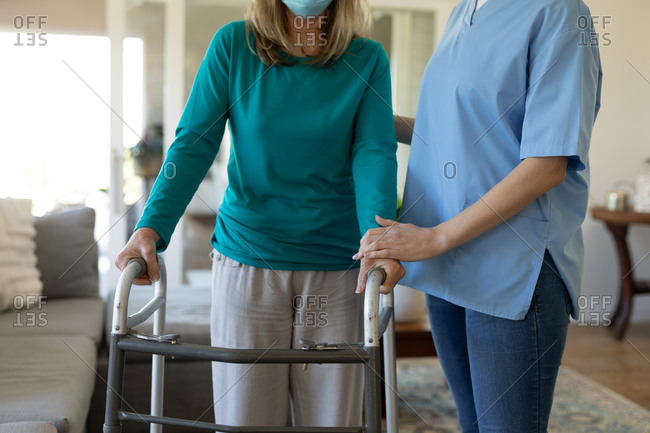 Senior Caucasian woman at home visited by Caucasian female nurse, walking using a walker, wearing face mask. Medical care at home during Covid 19 Coronavirus quarantine.
