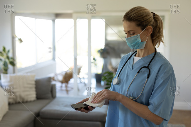 Caucasian female nurse, cleaning a smartphone with a tissue and wearing face mask. Medical care at home during Covid 19 Coronavirus quarantine.