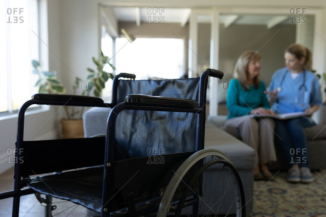 Senior Caucasian woman at home visited by Caucasian female nurse, sitting on couch, talking  with a wheelchair in foreground. Medical care at home during Covid 19 Coronavirus quarantine.