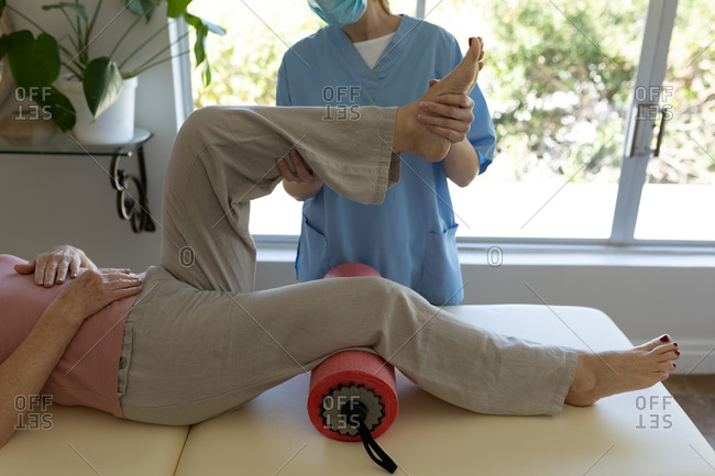 Senior Caucasian woman at home visited by Caucasian female nurse, stretching her leg, wearing face mask. Medical care at home during Covid 19 Coronavirus quarantine.