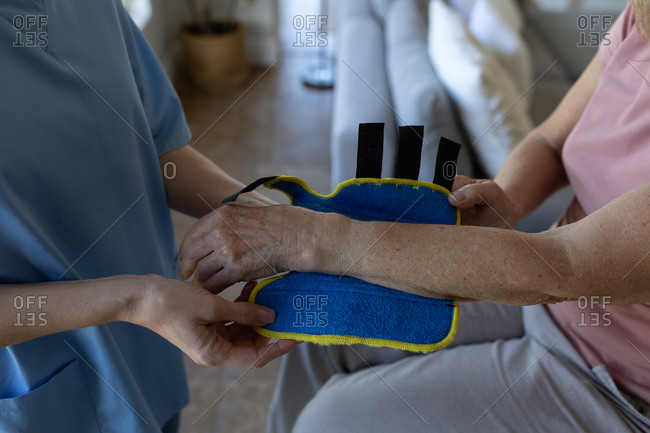 Senior Caucasian woman at home visited by Caucasian female nurse, putting on a wrist support. Medical care at home during Covid 19 Coronavirus quarantine.