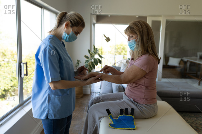 Senior Caucasian woman at home visited by Caucasian female nurse, stretching her wrist, wearing face masks. Medical care at home during Covid 19 Coronavirus quarantine.