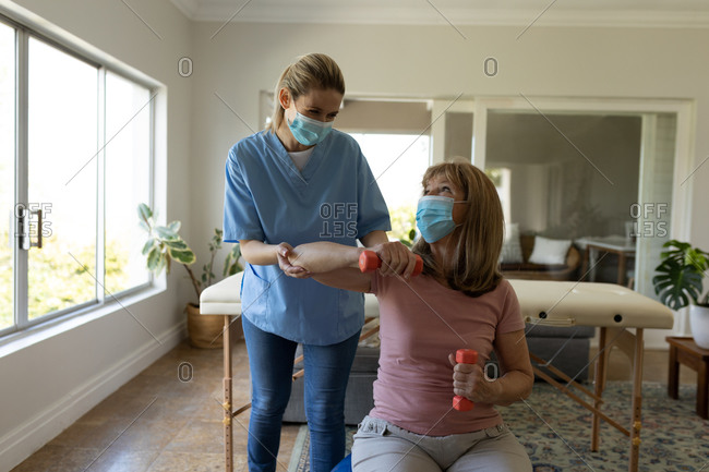 Senior Caucasian woman at home visited by Caucasian female nurse, stretching her arm, wearing face masks. Medical care at home during Covid 19 Coronavirus quarantine.