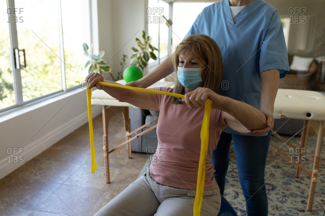Senior Caucasian woman at home visited by Caucasian female nurse, stretching arms using exercise band, wearing face mask. Medical care at home during Covid 19 Coronavirus quarantine.