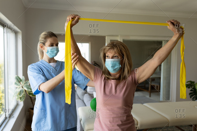 Senior Caucasian woman at home visited by Caucasian female nurse, stretching arms using exercise band, wearing face masks. Medical care at home during Covid 19 Coronavirus quarantine.