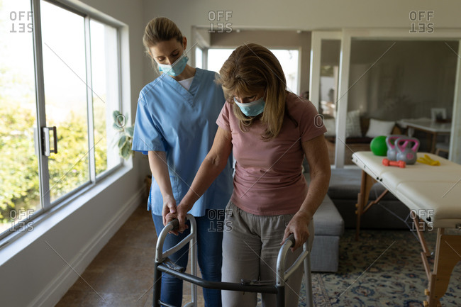 Senior Caucasian woman at home visited by Caucasian female nurse, walking using a walker, wearing face masks. Medical care at home during Covid 19 Coronavirus quarantine.