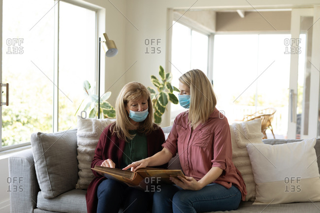 Senior Caucasian woman spending time at home with her adult daughter, sitting on couch, wearing face masks and reading a book. Social distancing during Covid 19 Coronavirus quarantine.