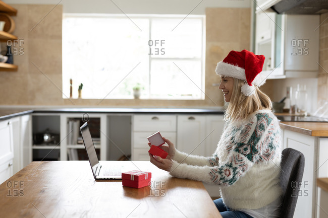 Caucasian woman spending time at home, sitting in kitchen at Christmas wearing Santa hat, using laptop with presents on table. Social distancing during Covid 19 Coronavirus quarantine.
