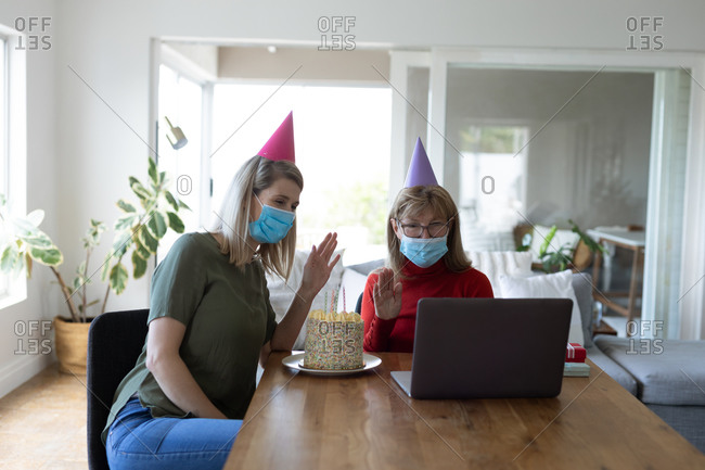 Senior Caucasian woman spending time at home with her adult daughter, sitting in living room with a birthday cake and using laptop. Social distancing during Covid 19 Coronavirus quarantine.