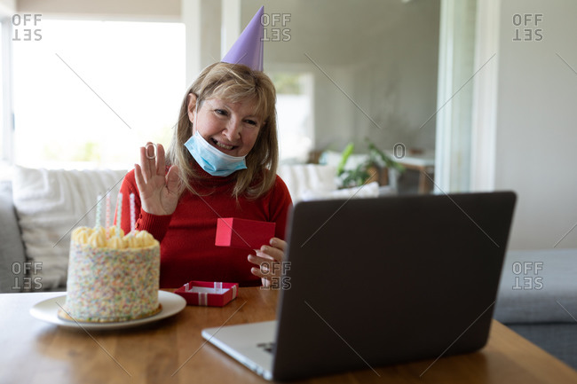 Senior Caucasian woman spending time at home, sitting in her living room with a birthday cake, wearing face mask and using laptop. Social distancing during Covid 19 Coronavirus quarantine lockdown.