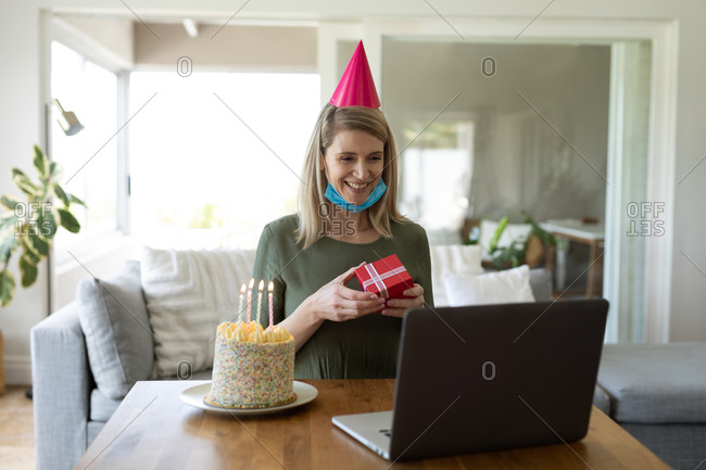Caucasian woman spending time at home, sitting in living room with birthday cake and using laptop. Social distancing during Covid 19 Coronavirus quarantine.