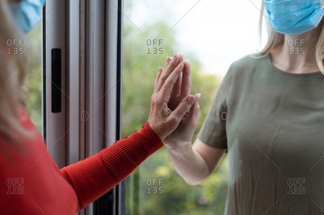 Senior Caucasian woman and her adult daughter at home, wearing face masks and greeting each other by touching hands. Social distancing, health and hygiene during Covid 19 Coronavirus pandemic.
