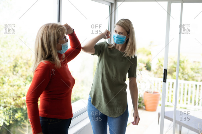 Senior Caucasian woman and her adult daughter at home, wearing face masks and greeting each other by touching elbows. Social distancing, health and hygiene during Covid 19 Coronavirus pandemic.