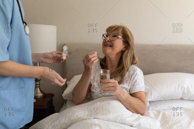 Senior Caucasian woman at home visited by Caucasian female nurse, taking medical pills. Medical care at home during Covid 19 Coronavirus quarantine.