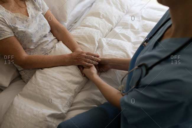 Senior Caucasian woman at home visited by Caucasian female nurse, sitting on bed, holding hands. Medical care at home during Covid 19 Coronavirus quarantine.