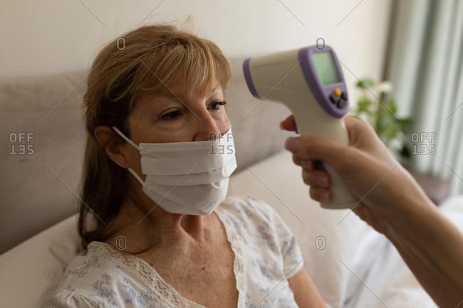 Senior Caucasian woman at home visited by Caucasian female nurse, checking temperature. Medical care at home during Covid 19 Coronavirus quarantine.