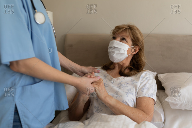 Senior Caucasian woman at home visited by Caucasian female nurse, standing and holding hands. Medical care at home during Covid 19 Coronavirus quarantine.