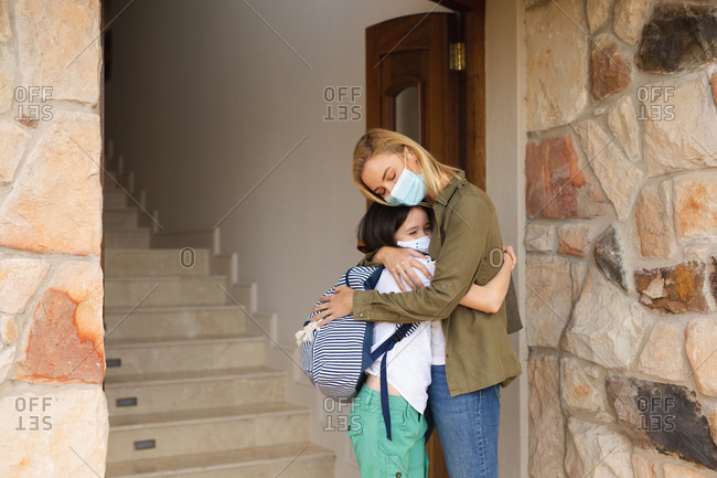 Caucasian woman and her daughter entering house, wearing face masks, standing next to door and embracing. Social distancing during Covid 19 Coronavirus quarantine lockdown.